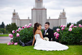 Romantic bride and groom in park surrounded by peony flowers — Stock Photo