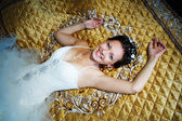 Happy bride on a luxury bed — Stock Photo