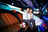Bride and groom in wedding limo — Stock Photo