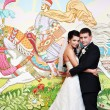 Happy bride and groom on background picture of fairy tales — Stock Photo