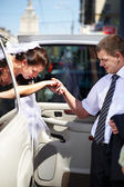 Gallant groom helping his bride out of a wedding limousine — Stock Photo