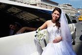 Happy bride near wedding limo — Stock Photo