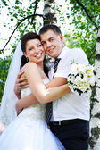 Happy bride and groom at the birches — Stock Photo