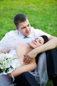 Happy bride and groom on grass — Stock Photo