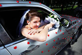 Beautiful bride in a wedding limousine — Stock Photo