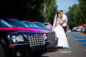 Happy bride and groom near wedding limousines — Stock Photo