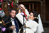 Happy bride and groom near metal tree with symbol lock — Stock Photo