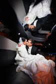 Gentle kiss bride and groom in wedding limo — Stock Photo