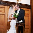 Stock Photo: Romantic kiss bride and groom on solemn registration of marriage
