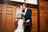 Romantic kiss bride and groom on solemn registration of marriage — Stock Photo