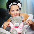 Stock Photo: Happy bride with teddy bear on white bed