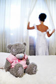 Bride near window and teddy bear on white bed — Stock Photo