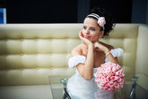 Beautiful bride with bouquet of flowers on modern interior — Stock Photo