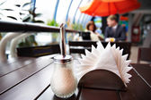Sugar bowl and napkins in cafes and in the background a man and  — Stockfoto