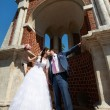 Romantic kiss bride and groom near ancient building — Stock Photo