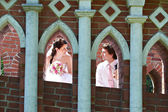 Happy bride and groom in windows of brick wall — Stock Photo