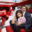 Bride and groom in wedding limousine — Stock Photo