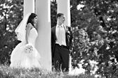 Bride and groom at wedding walk around column — Stock Photo