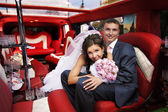 Bride and groom in wedding limousine — Стоковое фото