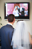 Bride and groom watch the video of his wedding — Stock Photo
