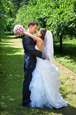 Happy bride and groom embrace in shady alley — Stock Photo