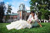Happy bride on grass in summer park — Zdjęcie stockowe