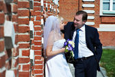 Happy bride and groom near red brick wall — Stock Photo