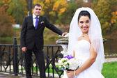 Joyful bride and groom in rainy weather — Stock Photo