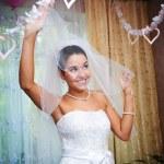 Happy bride plays her veil — Stock Photo #43758953