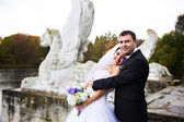 Happy bride and groom near ancient monument — Stock Photo