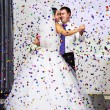 Dance of bride and groom in multi-colored confetti — Stock Photo