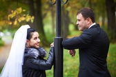 Happy bride and groom in autumn park — 图库照片