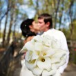 Bouquet kala against romantic kiss bride and groom — Stock Photo