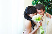 Happy bride and groom with bouquet — Stock Photo