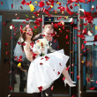 Happy newlyweds bride and groom with petals — Stock Photo #44494331