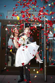 Happy newlyweds bride and groom with petals — Stock Photo