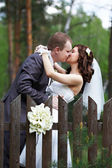 Kiss bride and groom about wooden fence — Stock Photo