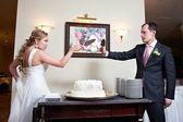 Funny bride and groom near wedding cake — Stock Photo