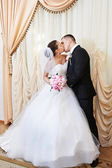 Happy bride and groom kissing on solemn registration — Stock Photo