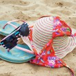 Hat, sunglasses, bikini and flip-flops on the sand — Stock Photo #48226161