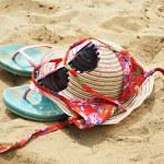 Hat, sunglasses, bikini and flip-flops on the beach — Stock Photo #48226227