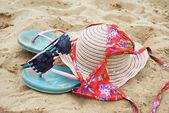 Hat, sunglasses, bikini and flip-flops on the sand — Stock Photo