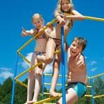 Three cheerful children on bar at the playground — Stock Photo #51417785