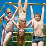 Three cheerful children on bar at the playground — Stock Photo #51418447