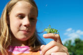 Girl with a grasshopper on a hand — Stock Photo