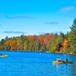Autumn lake and people on boats — Stockfoto