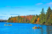 Autumn lake and people on boats — Stock Photo