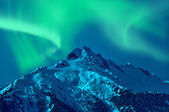 Snowy mountain with northern lights — Stock Photo