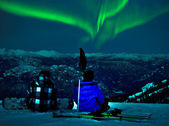 Northern lights over snow mountain peak — Stockfoto