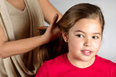 Mother combing her daughter — Stock Photo
